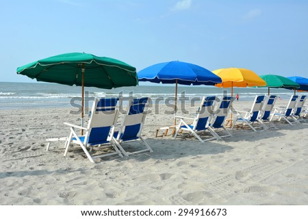 Row of beach chairs and umbrellas on the beach  - stock photo