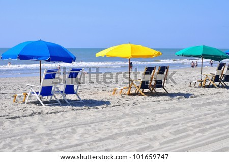 Row of beach chairs waiting for sun bathers - stock photo