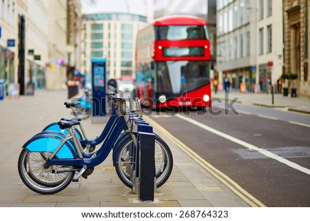 Row of bicycles for rent with red double-decker bus in the background on a street of London, UK - stock photo