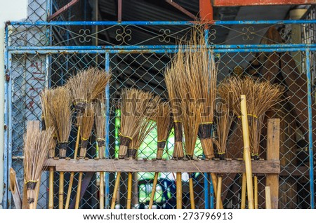 Row of big broom made from stems of coconut leaves. Coconut leave broom - stock photo