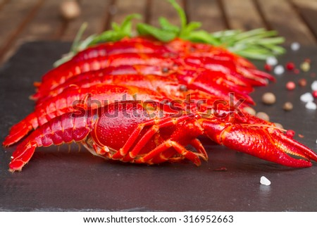 Row of big  red boiled  Crayfish on black board with spices - stock photo