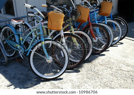 Row of bikes with baskets in a bike rack in a city - stock photo