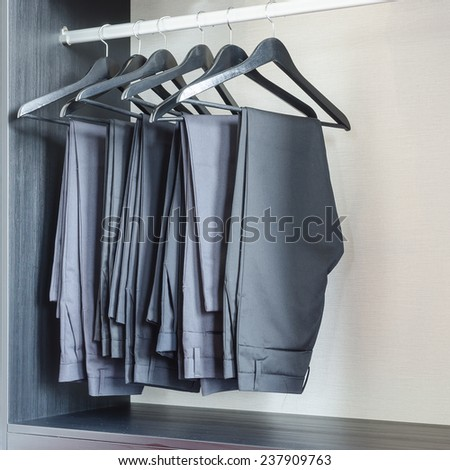 row of black pants hangs in wardrobe at home - stock photo