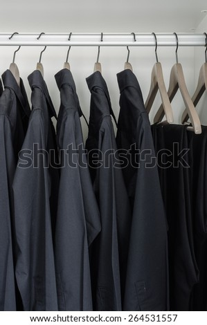 row of black shirts and pants hanging on coat hanger in white wardrobe - stock photo