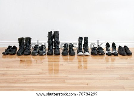 Row of black shoes and boots on a wooden floor, in front of a white wall. - stock photo