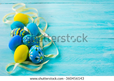 Row of blue hand-painted Easter eggs with satin ribbon on blue wood plank. Easter background. Easter symbol. Top view with copy space - stock photo