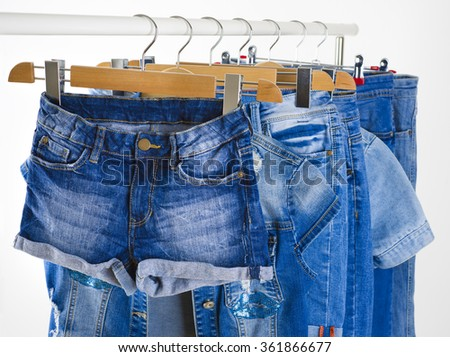 Row of blue jeans clothes on hangers in a shop - stock photo