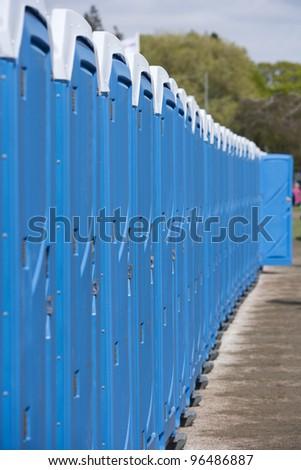 Row of Blue Portable Toilets - stock photo