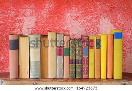 row of books, free copy space on red background - stock photo