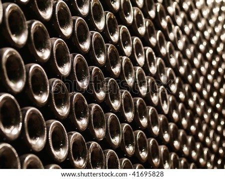 Row of Bordeaux wine bottles stacked in a cellar with shallow depth of field - stock photo