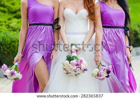 Row of bridesmaids with bouquets at big wedding ceremony. - stock photo