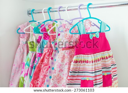 row of bright colorful little girl dresses hanging on coat hanger in white wardrobe - stock photo