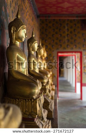 Row of Buddha images in sitting posture at Arun temple , bangkok, Thailand, with ancient Chinese style water color painting on the wall and background.  - stock photo