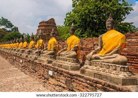 Row of Buddha statues in meditation at Wat Yai Chaimongkon temple in Ayutthaya, Thailand - stock photo