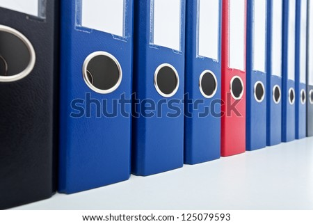 Row of business archive folders - with one prominent red in the middle - stock photo