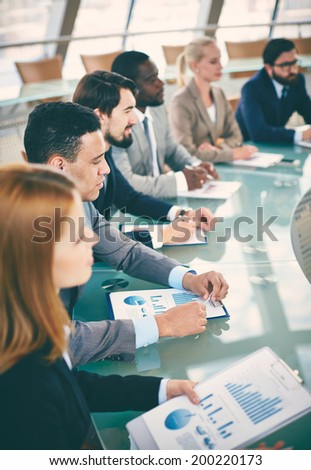 Row of business people listening to presentation at seminar - stock photo