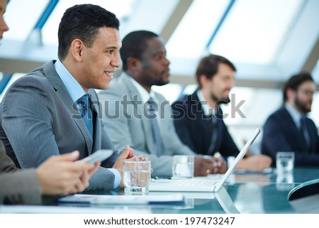 Row of business people listening to presentation at seminar with focus on elegant young man - stock photo
