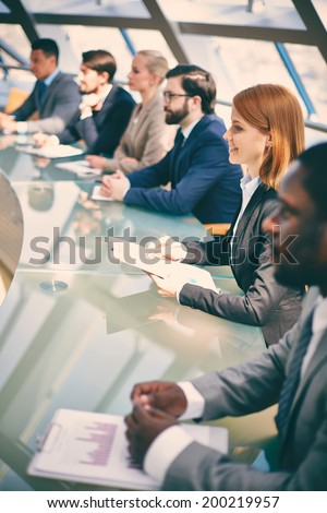 Row of business people listening to presentation at seminar with focus on smiling woman - stock photo