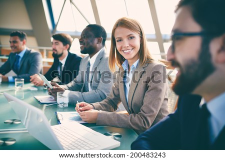 Row of business people listening to presentation at seminar with focus on smiling woman looking at camera - stock photo