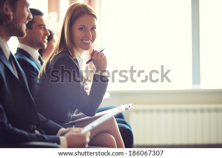 Row of business people sitting at seminar, focus on attentive young female - stock photo