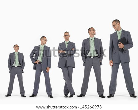 Row of businessmen in ascending order of height against white background - stock photo