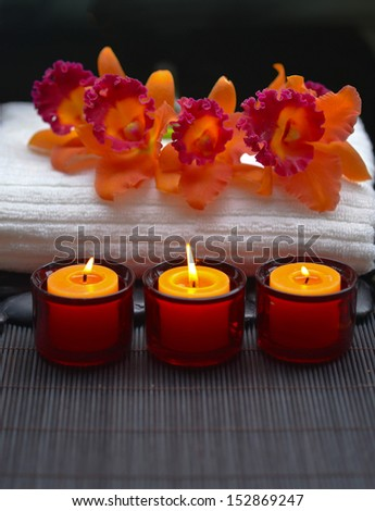 Row of candle with red orchid on towel and zen stones on mat  - stock photo