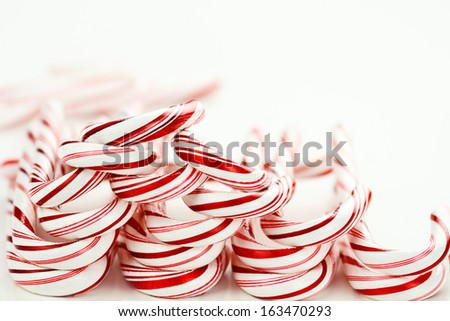 Row of candy canes on a white background with copy space. - stock photo