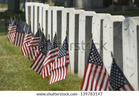 Row of cemetery headstones decorated with American Flags, close up - stock photo