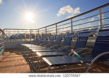 Row of chaise lounges on deck of cruise ship. Golden sun shining. - stock photo