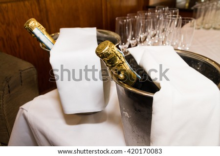 Row of champagne flutes and two bottles in ice buckets ready for pouring toast. - stock photo
