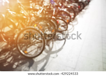 Row of city bikes on the parking with sunset light. Blurred background with place for text. - stock photo