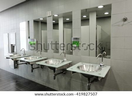 Row of clean and new sinks and taps in a public toilet - stock photo