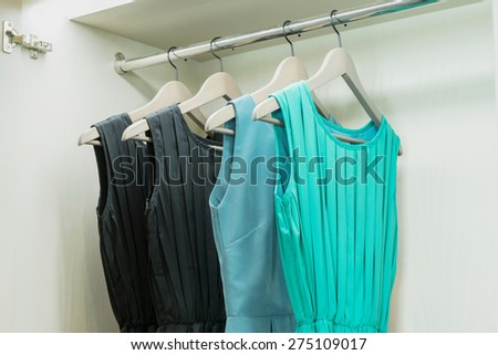 row of colorful dress hanging on coat hanger in white wardrobe - stock photo