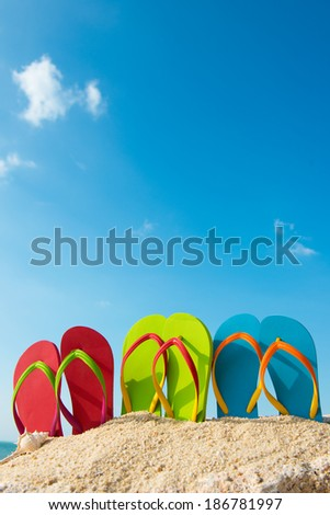 Row of colorful flip flops on beach against sunny sky - stock photo