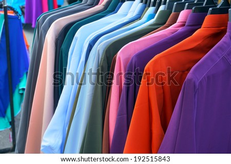 row of colorful row shirts hanging on - stock photo
