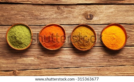 Row of colorful spices in bowls viewed from above on a wooden table with ginger, cayenne chili powder, turmeric and matcha or amchoor for Asian cuisine - stock photo