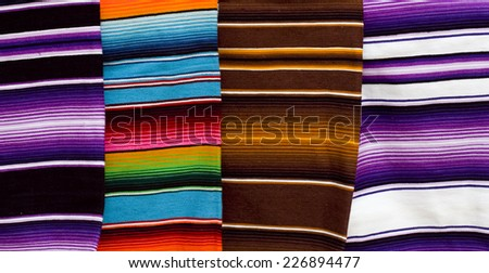 Row of colorful woven blankets for sale at Mexican market - stock photo