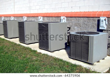 Row of commercial HVAC air conditioner outside condenser units outside a commercial building as part of a climate control cooling and refrigeration conditioning system - stock photo