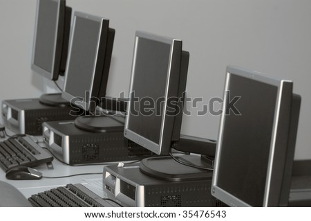 Row of computers set up for training at a classs room - stock photo