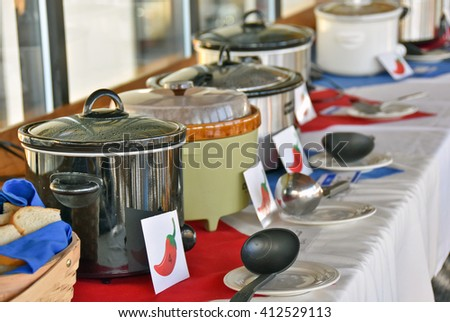 row of crock pots for chili cook off contest in restaurant - stock photo