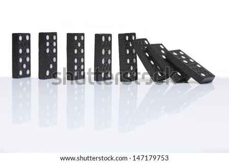 row of dominoes with one falling over  - stock photo
