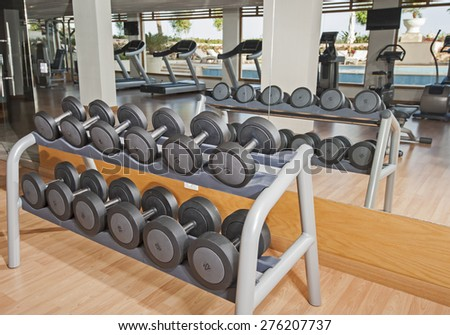 Row of dumbell weights on a rack in luxury health center gym - stock photo