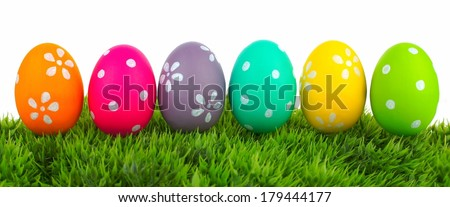 Row of Easter eggs on grass with a white background - stock photo
