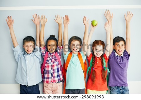 Row of ecstatic schoolmates with raised arms looking at camera - stock photo