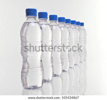 row of eight water bottles disappearing into distance with focus on front bottles - stock photo