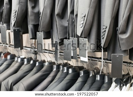 Row of elegant suits jacket on hangers in apparel store - stock photo