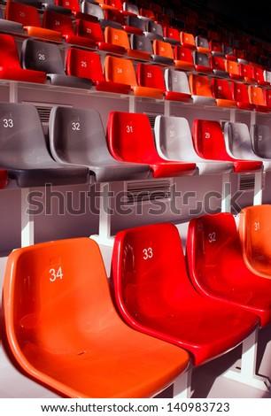 row of empty stadium seats colored - stock photo