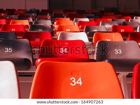 row of empty stadium seats colored - stock photo