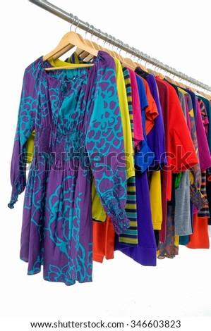 Row of female clothing hanging on hangers-white background   - stock photo