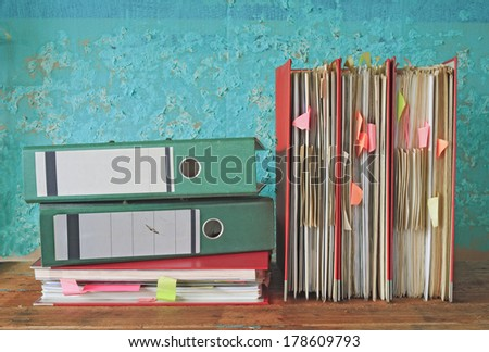 row of file folders with messy documents - stock photo